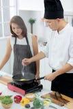 Asiatisk manlig kock som visar hur man lagar mat för härlig student royaltyfri bild