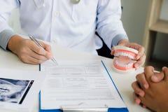 Asiatisk manlig lista för historia för patient för handstil för penna för tandläkarehandinnehav på anteckningsboken och diskussio royaltyfri fotografi