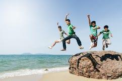 Asiatisk manlig tonåring som fyra hoppar och har gyckel på stranden royaltyfri foto