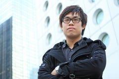 Asiatisk manstand framme av byggnad royaltyfri foto