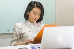 Asiatisk mapp för affärskvinnaläsningrapport i kontoret royaltyfria bilder