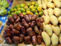 Asiatisk marknad, exotiska frukter rosa äpple, mango och mandarin royaltyfri fotografi