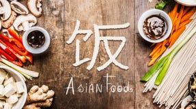 Asiatisk mat med olika grönsaker som lagar mat ingredienser på träbakgrund med den kinesiska hieroglyf av mat, bästa sikt Arkivbilder