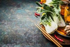 Asiatisk mat och ätabegrepp: Kinesisk eller thailändsk kokkonst och att laga mat ingredienser med pak choi och pinnar på mörk tap Royaltyfria Bilder