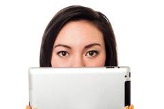 Asiatisk modell som döljer hennes framsida med minnestavlaapparaten Royaltyfria Foton