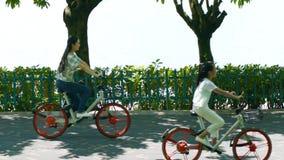 Asiatisk moder & dotter som cyklar på lakesidepromenad i sommar arkivfilmer