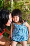 Asiatisk moder och dotter hemma i trädgård Fotografering för Bildbyråer
