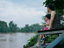 Asiatisk moder och hennes lilla dotter av hennes sida som ser den skumma leriga floden efter nederbörd arkivfoton