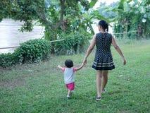 Asiatisk moder som rymmer hennes lilla dotters hand och att ha att gå tillsammans på ett utomhus- fält för grönt gräs vid flodstr arkivbilder