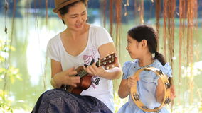 Asiatisk moder som spelar ukulelet för hennes dotter