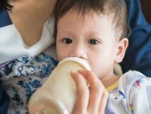 Asiatisk modermatning mjölkar henne behandla som ett barn vid flaskan Arkivfoto