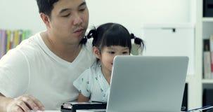 Asiatisk modern familj och liten flicka, medan farsan arbetar med anteckningsboken stock video