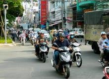 Asiatisk mopedfolkmassatrafik på gatan Arkivbild