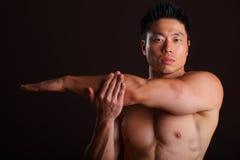 Asiatisk muskulös man som sträcker den vänstra armen Arkivbild