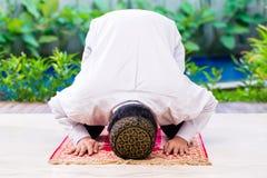 Asiatisk muslimsk man som ber på matta Royaltyfria Foton