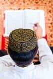 Asiatisk muslimsk man som studerar Koranen eller Quran Royaltyfri Bild