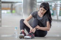 asiatisk olycka för ben för skada för ung kvinna för kondition körande av genomköraren som övar på gatan i stads- stad sammanträd royaltyfri foto