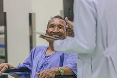 Asiatisk patient i rullstolsammanträde i sjukhus med asiatisk docto royaltyfria foton