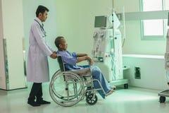 Asiatisk patient i rullstolsammanträde i sjukhus med asiatisk docto royaltyfri fotografi