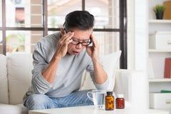 Asiatisk pensionär med sträng huvudvärk royaltyfria bilder