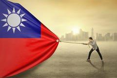 Asiatisk person som drar flaggan av Taiwan Arkivfoton