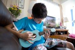Asiatisk pojke för barnpanna som öva på hans blåa ukelele i en hem- miljö Royaltyfria Bilder
