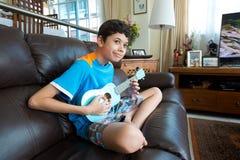 Asiatisk pojke för barnpanna som öva på hans blåa ukelele i en hem- miljö Royaltyfri Fotografi