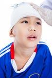 Asiatisk pojke i blå sportswear med trauman av huvudet royaltyfri fotografi