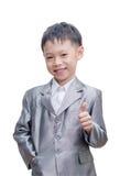 Asiatisk pojke i dräkt som ler med tummen upp Arkivbilder