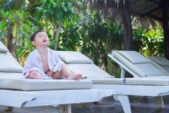 Asiatisk pojke med den vita handduken som vilar på en vardagsrumsolstol eller sol Royaltyfri Bild