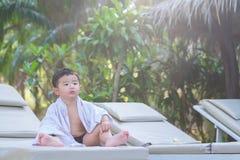 Asiatisk pojke med den vita handduken som vilar på en vardagsrumsolstol eller sol Arkivfoton