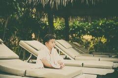 Asiatisk pojke med den vita handduken som vilar på en vardagsrumsolstol eller sol Royaltyfri Fotografi