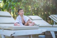 Asiatisk pojke med den vita handduken som vilar på en vardagsrumsolstol eller sol Arkivfoto