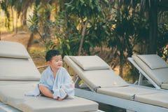 Asiatisk pojke med den vita handduken som vilar på en vardagsrumsolstol eller sol Arkivbild