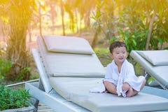 Asiatisk pojke med den vita handduken som vilar på en vardagsrumsolstol eller sol Arkivbilder
