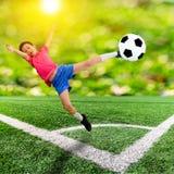 Asiatisk pojke med fotbollbollen på fotbollfält Arkivbild