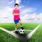 Asiatisk pojke med fotbollbollen på fotbollfältet Arkivfoton