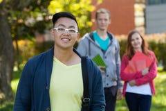 Asiatisk pojke och hans universitetvänner Arkivbild