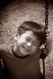 Asiatisk pojke på en swing Arkivbilder