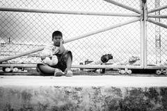 asiatisk pojke som är ledsen och bara sitter på dörren av flygplatsen ar Royaltyfria Bilder
