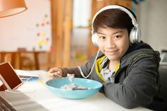 Asiatisk pojke som äter och spelar på minnestavladatoren arkivbilder