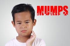 Asiatisk pojke som får sjuk med påssjuka royaltyfri bild