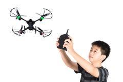 Asiatisk pojke som fungerar surret eller quadcopteren vid fjärrkontroll c Arkivfoton