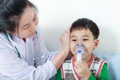 Asiatisk pojke som har den respiratoriska sjukdomen att hjälpas av vård- yrke arkivbilder