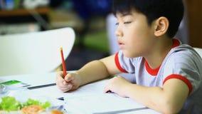 Asiatisk pojke som hemma gör läxa lager videofilmer