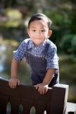 Asiatisk pojke som ler och ser rak in i kamera medan utomhus Royaltyfri Fotografi