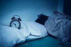 Asiatisk pojke som nära sover på säng, svart ringklocka för antikvitet förbi Arkivbild