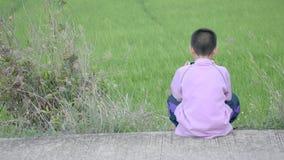 Asiatisk pojke som rymmer en telefon och sitter på gatabakgrunden de gröna risfälten lager videofilmer
