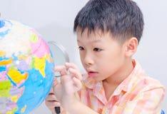 Asiatisk pojke som ser ett jordklot Arkivbild