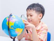 Asiatisk pojke som ser ett jordklot Arkivfoton
